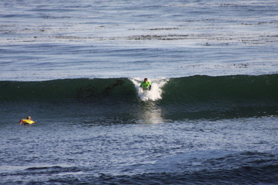 The surfer's arms are extended supporting his upper weight.