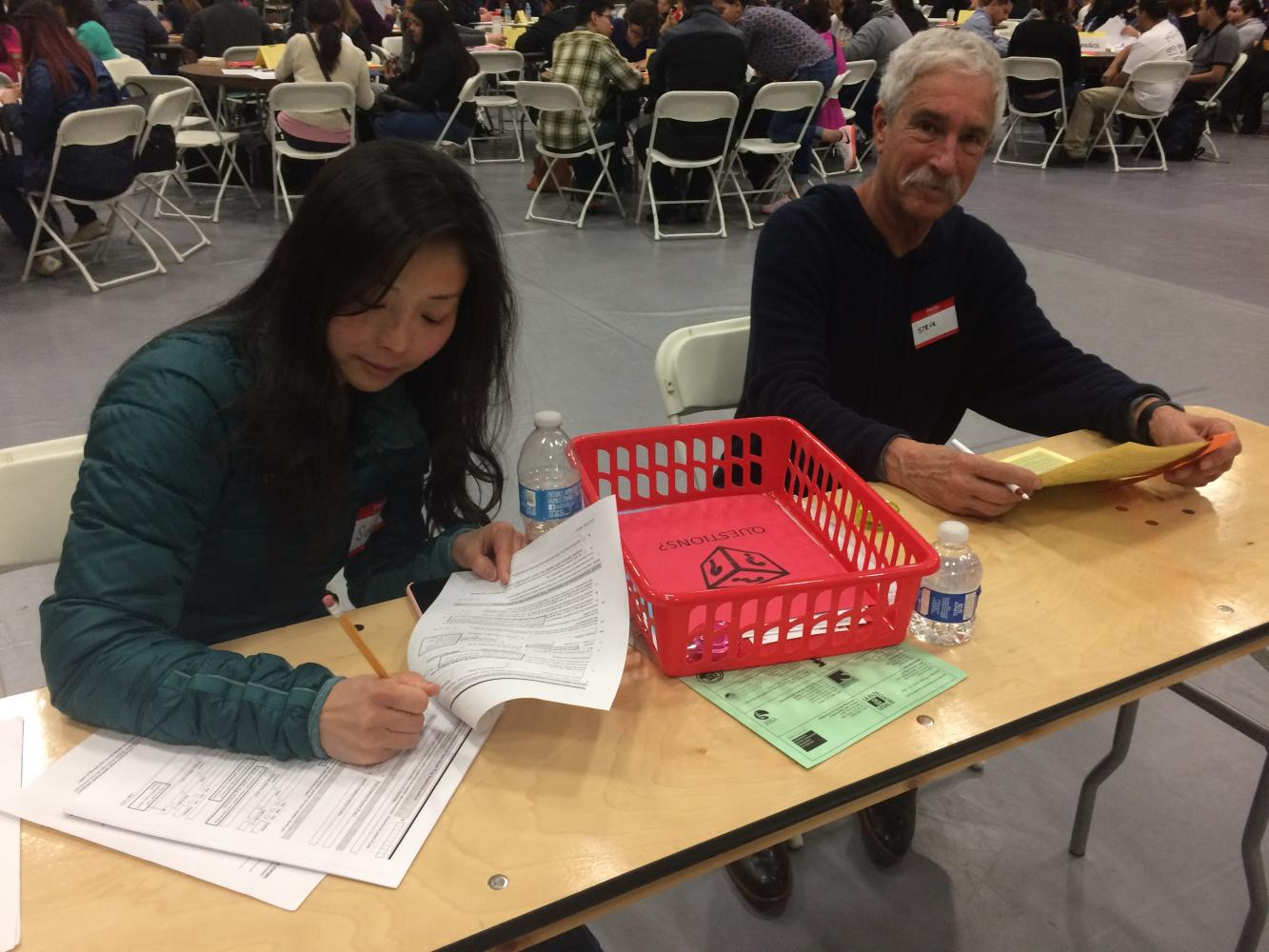 Immigration Workshop volunteers (left) Susan Jang and Steve Ravel help attendees fill out citizenship applications in the SJCC gym, Saturday April 22.