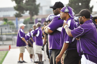 Team coaches discuss plays and strategies for the players on the sideline.