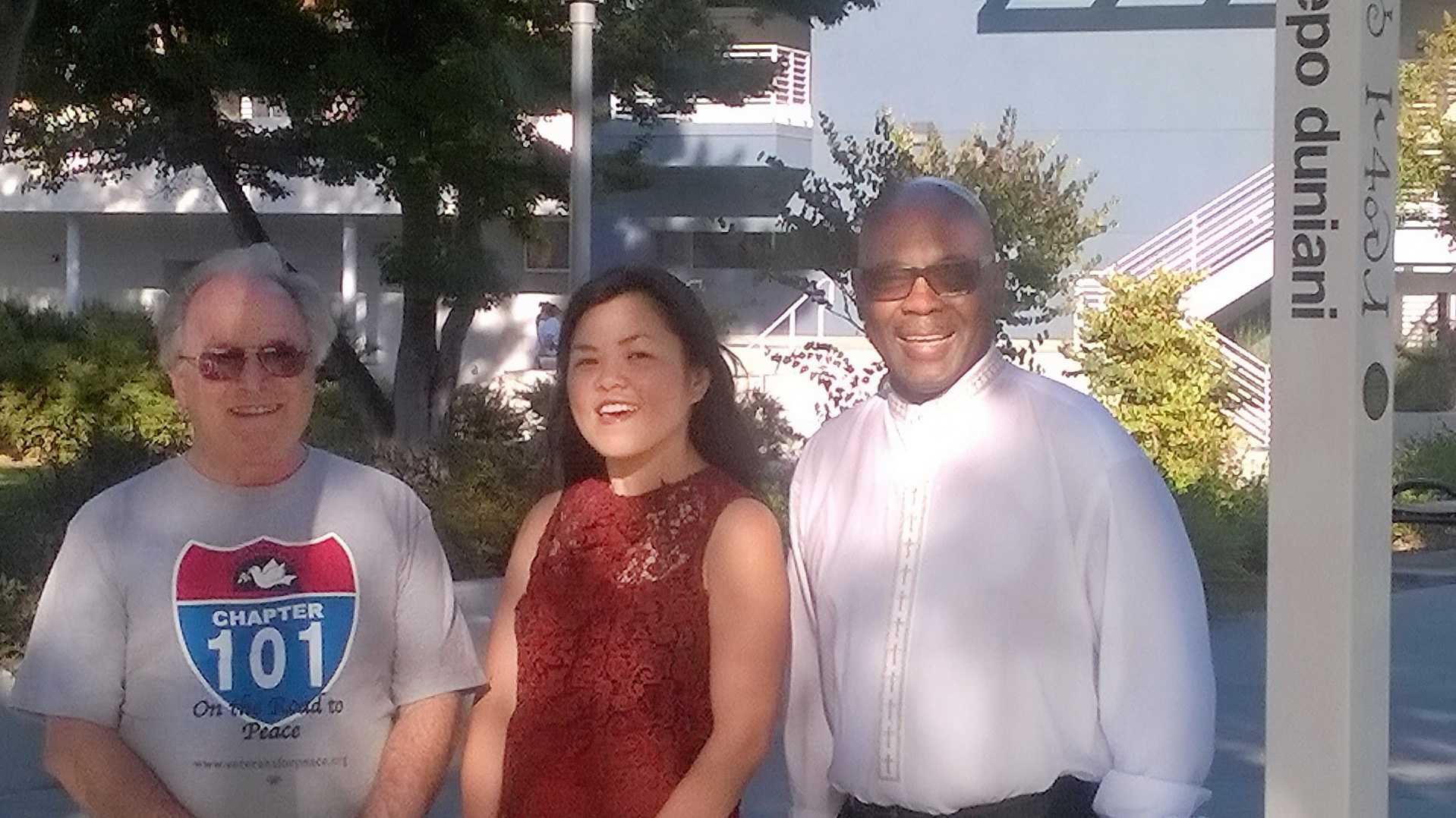 Philip Pflager, Cam Vu, Rev. Jethroe Moore II pose by peace pole