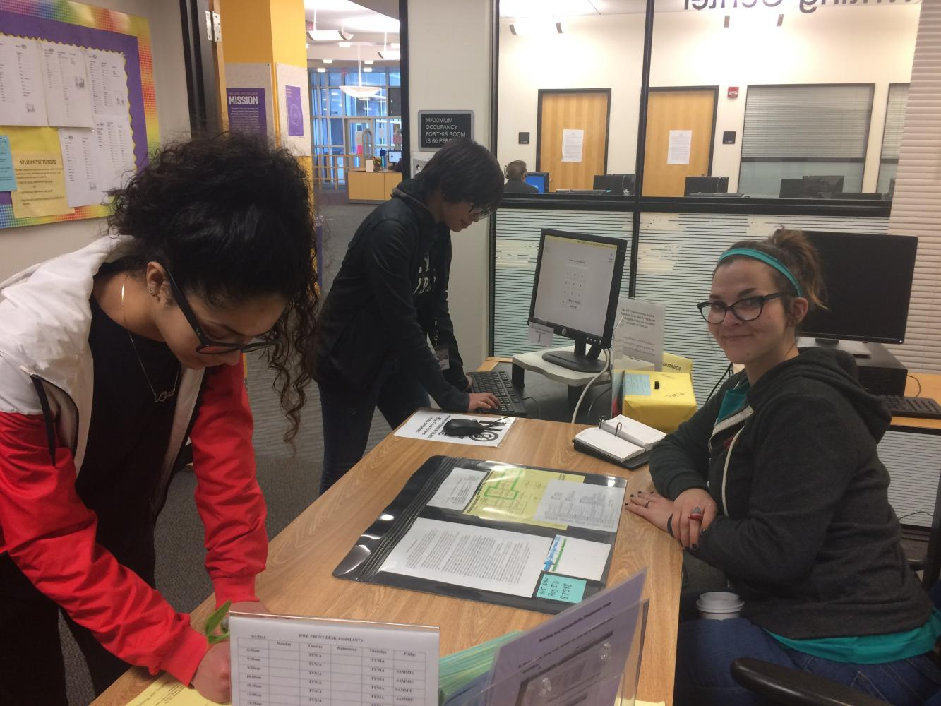 (Left) Peer tutors at the RWC Noor Basma, Lauren Apostle and Sammie Gilmore demonstrate how to sign in for a tutoring session.
