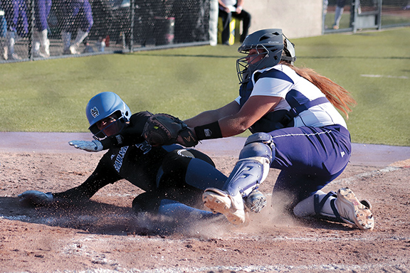 Jaguars Catcher Natasha Sachdeva (3) prevents a run from scoring by tagging out Bulldogs Short Stop Leaness Donn (3) before she can slide in to home plate during the top of the fifth inning. The Bulldogs would finish the inning with the lead scoring the first two runs of the game.