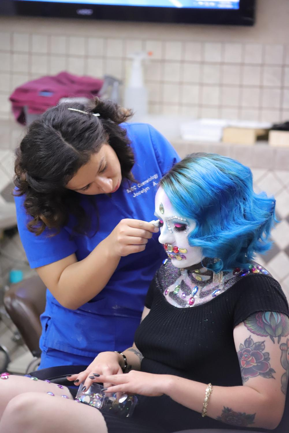 Model+Allison+Burns+looks+down+at+the+gem+stones+that+are+being+applied+to+her+by+technician+Jocelyn+Arias+during+the+2018+Cosmetology+Spring+Hair+Competition+held+in+the+cosmetology+building+at+SJCC+on+Friday%2C+April+27.+Arias+and+Burns+placed+Third+in+%E2%80%9CMakeup%E2%80%9D+and+Fourth+in+%E2%80%9CHair%E2%80%9D+at+the+Spring+Hair+show+held+at+the+Glasshouse+later+that+night.