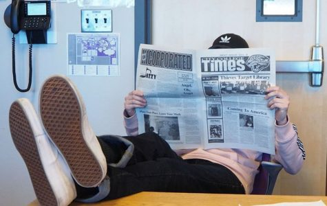 City College Times Editor-in-Chief Jasper Somera relaxes in the newsroom with a copy of the City College Times newspaper.