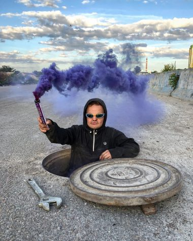Super Sus, popular YouTuber and urban explorer, emerges from an underground vault wielding a flare billowing purple smoke.  Photo courtesy of instagram user sssuper_sus.