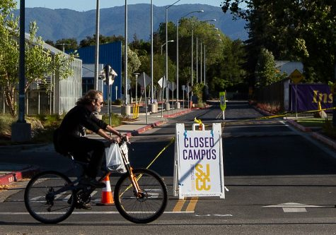 "A cyclist rides by a ""Campus Closed"" sign near San Jose City College on Moorpark Ave. on March 3. A return to in-person classes is being considered by SJECCD administrators for the fall semester if county health guidelines will permit it."