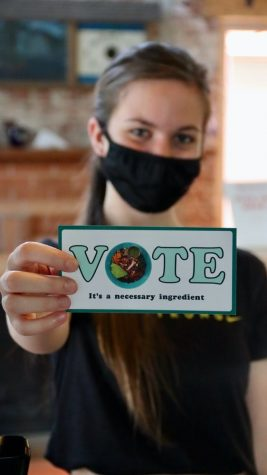 This photo from Unsplash images shows a woman promoting the idea to go out and vote.